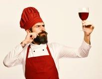 Szef kuchni trzyma szkło czerwone wino Cook z rozważną twarzą zdjęcia stock