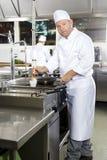 Szef kuchni używa muśnięcie przygotowywać naczynie w kuchni Obrazy Stock