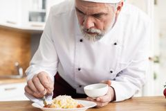 Szef kuchni uciera ser talerz z ?wie?ym makaronem zdjęcia stock