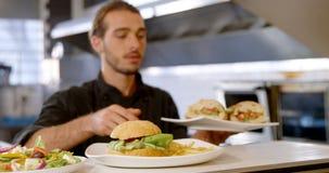 Szef kuchni utrzymuje talerze hamburger na rozkaz staci 4k zdjęcie wideo