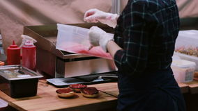 Szef kuchni w białych rękawiczkach robi hamburgerowi z świeżą sałatką, stawia pomidory each hamburger od zbiornika widok z powrot zbiory