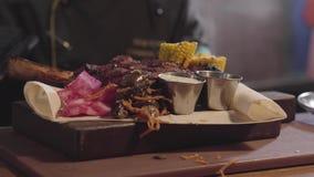 Szef kuchni w czarnych kuchenek rękawiczkach słuzyć na talerzu piec na grillu mięso, pokrajać kawałki piec kukurudza, kumberlandy zbiory