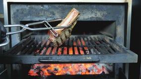 Szef kuchni w czarnych rękawiczkach z żelaznymi tongs obala dużego grubego stek który smaży na grillu, w górę strzału od  zbiory