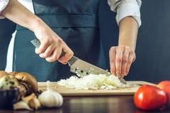 Szef kuchni w czarnym fartuchu ciie cebuli z nożem Pojęcie życzliwi produkty dla gotować Zdjęcia Stock