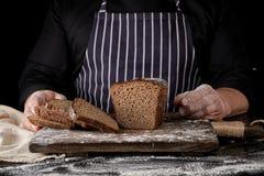 szef kuchni w czerń mundurze pokrajać piec żyto chleb na brąz drewnianej desce fotografia royalty free