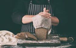szef kuchni w czerń mundurze pokrajać piec żyto chleb na brąz drewnianej desce kropiącej z białą mąką fotografia stock