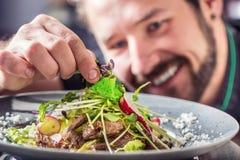 Szef kuchni w hotelowej lub restauracyjnej narządzanie sałatce z kawałkami wołowina zdjęcia royalty free