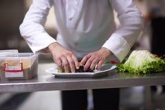Szef kuchni w hotelowym kuchennym narządzaniu i dekorować jedzeniu Obrazy Royalty Free