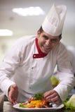 Szef kuchni w hotelowym kuchennym narządzaniu i dekorować jedzeniu Zdjęcie Stock