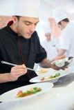 Szef kuchni w restauracyjnym narządzania naczyniu Obrazy Stock