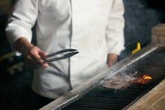 Szef kuchni wołowiny kulinarny stek na bbq w restauracyjnej kuchni obrazy stock