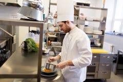 Szef kuchni z garnka kucharstwem i porci jedzenie przy kuchnią Zdjęcia Stock