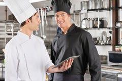 Szef kuchni Z kolegą Trzyma Cyfrowej pastylkę Zdjęcia Royalty Free