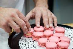 Szef kuchni z macaroons na tacy przy piekarnią Fotografia Stock