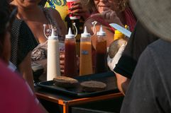 Szef kuchni z nożem, ciie hamburgeru chleb dla tłumu Szczególnie kumberlandy opierający się na majonezie, chwyt w górę, mustar obrazy stock