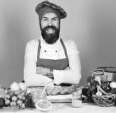Szef kuchni z pikantność, warzywami i ciastem na stole, Cook z rozochoconą twarzą w Burgundy jednolitych pobliskich składnikach Obrazy Royalty Free