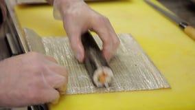 Szef kuchni z rękawiczkami na koloru żółtego stole tworzy rolki z matą zbiory