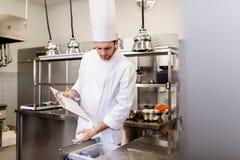 Szef kuchni z schowkiem robi inwentarzowi przy kuchnią Obraz Stock