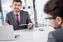 Szef patrzeje kolegi przy biznesowym spotkaniem z dokumentami fotografia stock