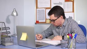 Szef siedzi przy biurkiem sprawdza dokumenty dokąd laptopów stojaki zdjęcie wideo