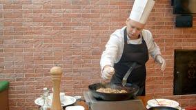 Szefa kuchni ściśnięcia cytryny sok w nieckę z paella Obraz Royalty Free