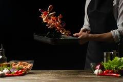 Szefa kuchni czas gotować świeżej garneli w niecce, marznie w ruchu z warzywami Kulinarny owoce morza, zdrowy jarski jedzenie i j zdjęcia royalty free
