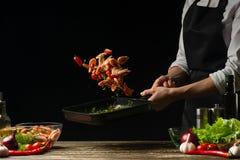 Szefa kuchni czas gotować świeżej garneli w niecce, marznie w ruchu z warzywami Kulinarny owoce morza, zdrowy jarski jedzenie i j obrazy stock