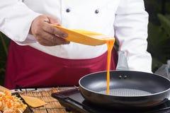 Szefa kuchni dolewania jajko niecka obrazy stock