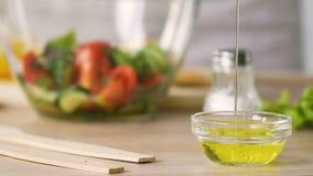 Szefa kuchni dolewania oliwa z oliwek pomiarowy puchar, opatrunkowa sałatka, gotuje zdrowego jedzenie zbiory