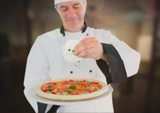 Szefa kuchni dolewania oregano pizza w restauraci Zdjęcie Stock