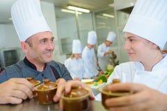 Szefa kuchni i praktykanta mienia ramekin garnki obraz royalty free
