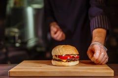 Szefa kuchni kładzenia babeczka na wierzchołku, on robi wołowina hamburgerowi dla klienta rozkazu zdjęcia royalty free
