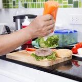 Szefa kuchni kładzenia majonez na hamburger babeczce zdjęcia royalty free