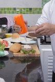 Szefa kuchni kładzenia majonez na hamburger babeczce obraz royalty free