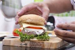 Szefa kuchni kucharstwo i dekorujący hamburger obraz stock