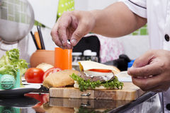 Szefa kuchni kucharstwo i dekorujący hamburger fotografia stock