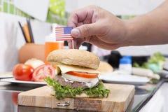 Szefa kuchni kucharstwo i dekorujący hamburger z flaga amerykańską zdjęcia stock