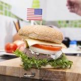 Szefa kuchni kucharstwo i dekorujący hamburger z flaga amerykańską zdjęcia royalty free