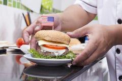 Szefa kuchni kucharstwo i dekorujący hamburger z flaga amerykańską obraz stock