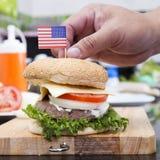Szefa kuchni kucharstwo i dekorujący hamburger z flaga amerykańską fotografia stock