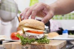 Szefa kuchni kucharstwo i dekorujący hamburger Obraz Royalty Free