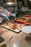 Szefa kuchni kucharstwo piec na grillu ryby w bufet restauracji zdjęcia stock