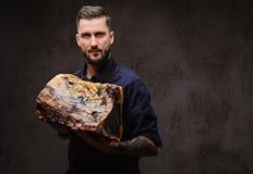 Szefa kuchni kucharz trzyma wielkiego kawałek wyłączność na wywiad leczący mięso na ciemnym tle zdjęcie stock