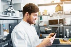 Szefa kuchni kucharz z pastylka komputerem osobistym przy restauracyjną kuchnią zdjęcia stock