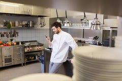 Szefa kuchni kucharz z smartphone przy restauracyjną kuchnią zdjęcia stock