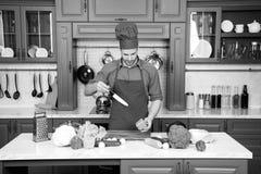 Szefa kuchni Kulinarny jedzenie W kuchni Mężczyzna szefa kuchni kucharz z nożem w kuchni, kuchnia Warzywa i narzędzia dla na stoł obraz royalty free