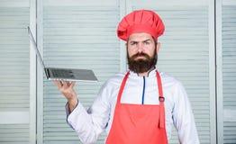 Szefa kuchni laptop przy kuchnią Kulinarna szkoła Modniś w kapeluszu i fartuch kupujemy produkty online TARGET128_1_ online tło p zdjęcie stock