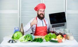 Szefa kuchni laptop przy kuchni? Kulinarna szko?a Modni? w kapeluszu i fartuch kupujemy produkty online TARGET128_1_ online M??cz obraz stock