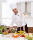 Szefa kuchni męski portret na białym countertop przy kuchnią Obrazy Royalty Free