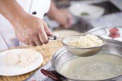 Szefa kuchni mienia colander z gotującym kluski zdjęcia royalty free